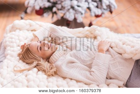 Sweet dreams. Nice happy blonde woman lying on the knitted plaid and smiling while dreaming about something