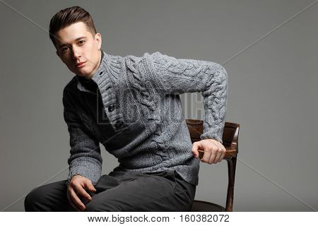 Sexy young man in warm knit sweateron a gray background . Male model.