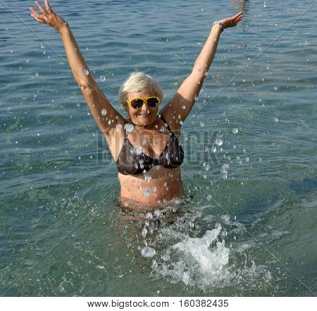 Aged Woman Is Doing Splashing Motions In Clear Sea Water.