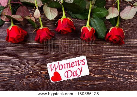 Flowers with Women's Day card. Red roses and wooden background. Cherish your sweetheart. Romantic gift on holiday.
