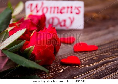 Roses near Women's Day card. Hearts and flowers. Complete your gift with bloom. Petals of joy.