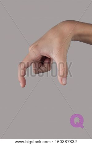 Symbol Q in gesture language. Letter made by human hand on grey background