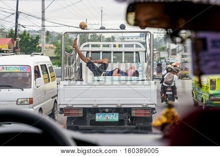 Cebu. Philippines - 19 oct. 2016: Man is sleeping in truck body on roadway while transport is moving at peak hour at gray day