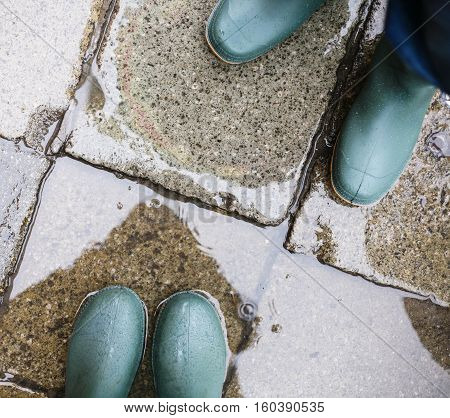 legs in green rubber boots in puddle in rainy day in Venice