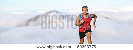 Trail runner man athlete running in mountains outdoor nature with mountain peak in clouds in background. Panorama horizontal banner landscape crop for copyspace.
