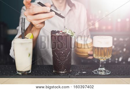 Barman offers exotic sweet cocktails in restaurant. Professional bartender's hands make drinks in night club bar. Selective focus on glasses