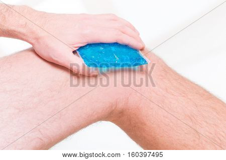 Man using cold gel compress on knee to reduce pain
