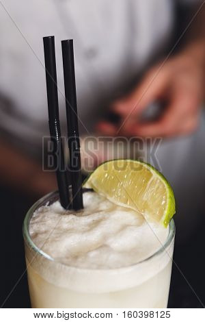 Closeup of frothy coconut pina colada cocktail at barmen's hands background. Refreshing drink with lime. Party time background