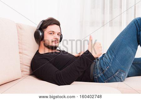 Man Laying On Sofa Wearing Headphones Showing Thumb Up