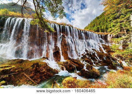 The Nuo Ri Lang Waterfall (nuorilang) Among Fall Forest