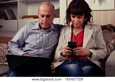 A mid shot of a cute couple regarding something on their devices. Man in shirt seriously looking at his laptop, smiling woman playing with a phone