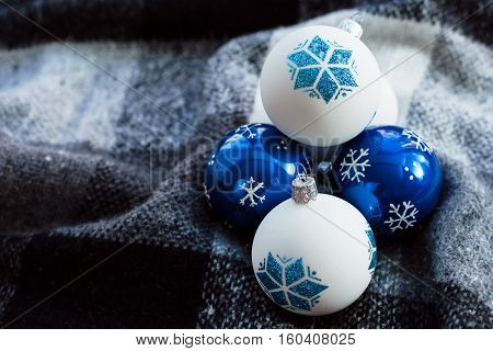 Christmas toy balls of blue and white lying on plaid