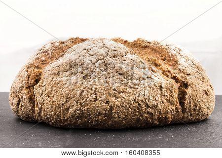freshly baked brown irish soda bread with flour on slate
