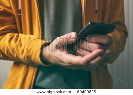 Unlocking smartphone with fingerprint scan sensor man using modern security technology feature to authenticate access and use device