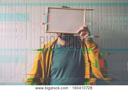 Unrecognizable man posing with blank picture frame over his face as copy space digital glitch effect added in post production