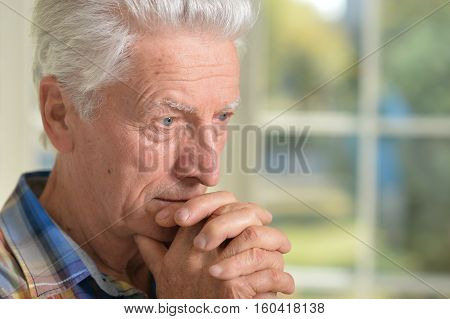 Portrait of thoughtful senior man with clasped hands