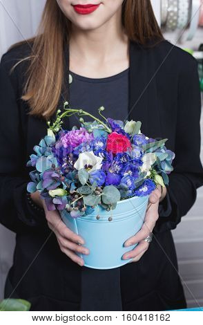 Woman carrying metal bucket with fresh flowers, florist shop
