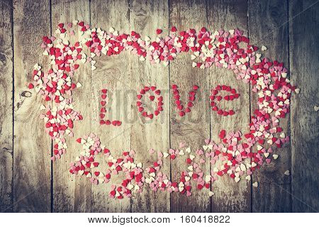 Love concept with letters LOVE and sweethearts on old wooden background vintage toning. Top view with copy space