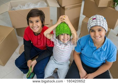 Happy kids with boxes at new modern home top view