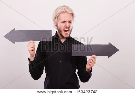Planning directions choices concept. Furious angry man holding black arrow pointing left and right in opposite directions. Indoor shot on light background