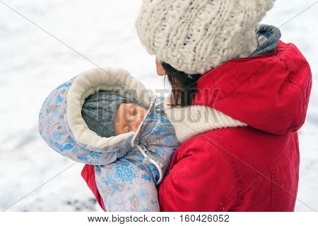 Mom holds the baby in her arms wrapped the baby in overalls winter day hat and gloves red coat