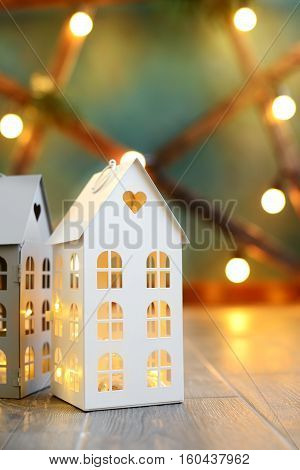 Little Toy Christmas Houses With A Burning Light Inside Is On Blured Green Background