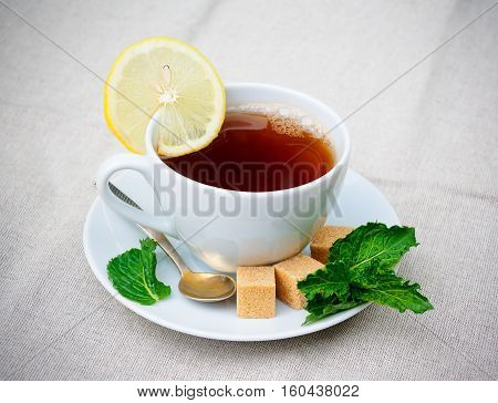 Tea with mint brown sugar and lemon on table. Selective focus