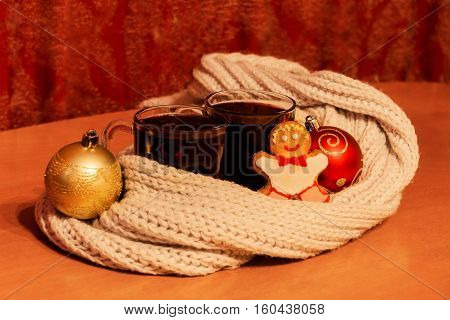Glasses of mulled wine wrapped scarf christmas cookie and christmas balls. Selective focus