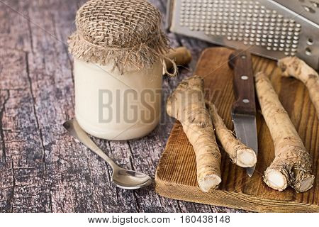 The root of horseradish, a metal grater and a jar with  seasoning on old wooden table.
