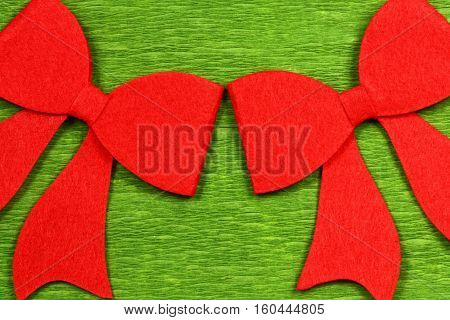 Two red felt bows on green background. Christmas decoration