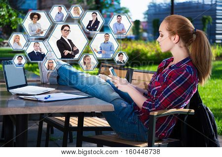 social network and internet addiction concept - teenage girl sitting in cafe with smart phone and laptop