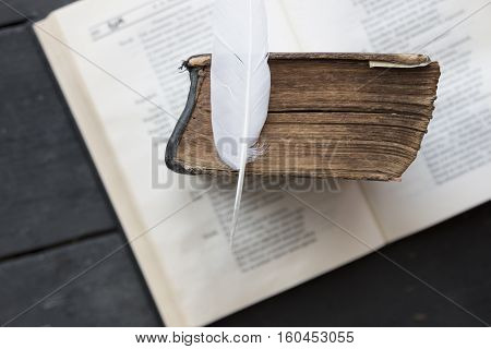 College courses concept Vintage book and feather on the old wooden table.