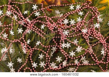 Christmas festive decoration of fir branches beads snowflakes. Christmas and New Year's background.