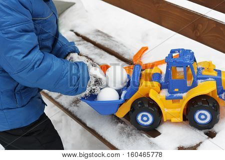 Children's winter games outdoors. The image of a child making snow snow balls and playing with a large colourful toy car.