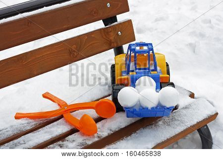 Children's winter games outdoors.Large toy car and other baby toys are on the bench covered with snow.