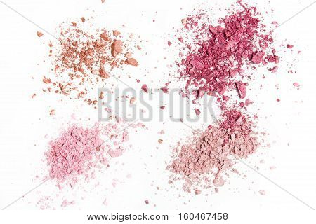 Crumbled eye shadows four different colors on a white background. The palette shiny eye shadow.