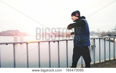 The athlete doing workout on a city bridge on the sunset