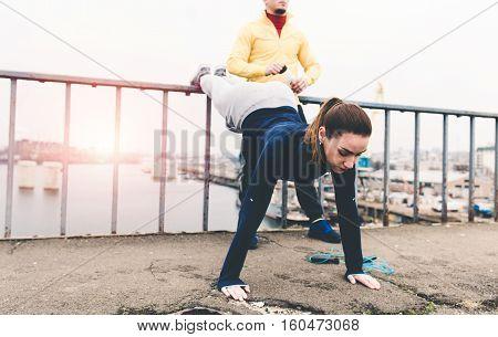 Couple of athletes doing workout on a city bridge on the sunset