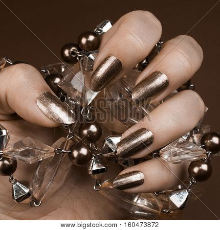 Female hand with shiny brown nails holds brown jewel on brown background.