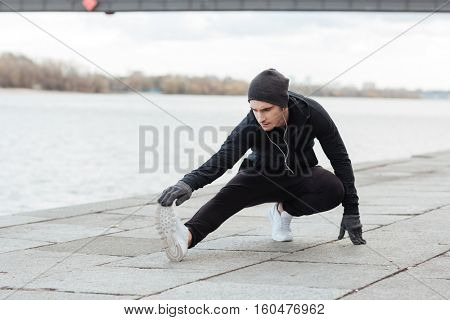 Attractive young man athlete doing exercises after running outdoors
