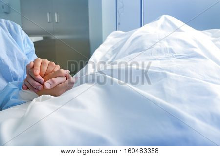 Wife holds the hand of the deceased spouse in the hospital.
