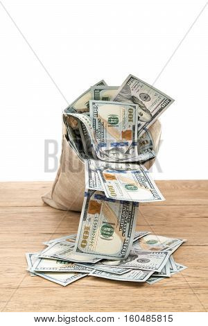 Bag with money falls and out of it falling dollars on an old wooden table isolated on white background