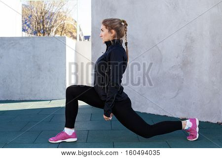 Young fitness woman doing front lunge gray wall background