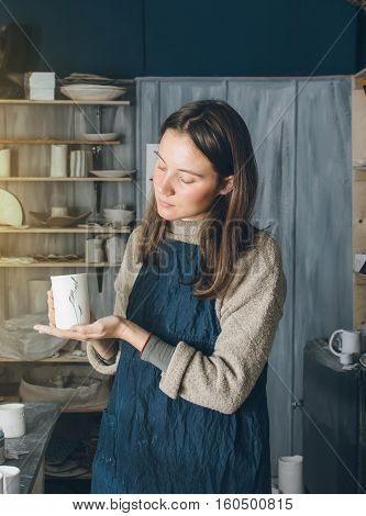 Woman holding cup of ceramic in her workshop