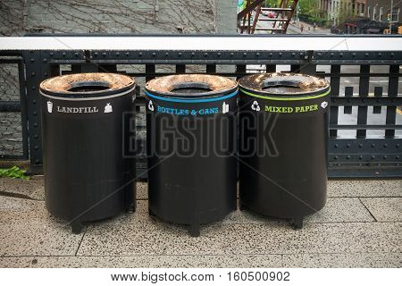 three trash bins for different types of garbage in the streets of new york