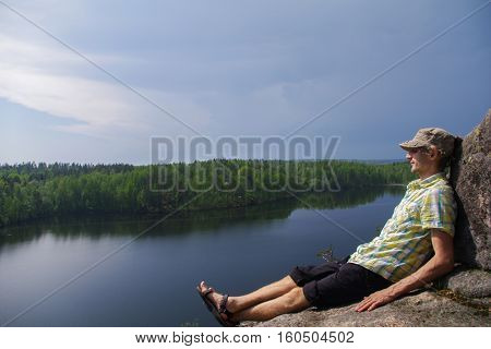 a happy young man sitting on a rocky above a lake