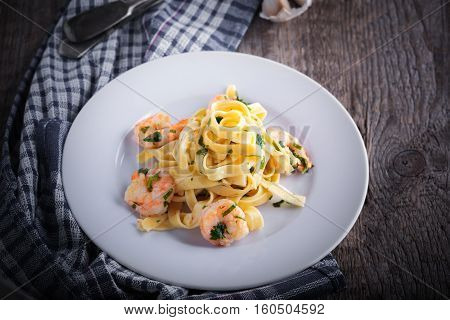 Tagliatelle with shrimps on a white plate