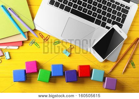 Laptop, copybook and wooden cubes on color background