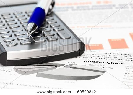 Calculator and pen on the  budget charts