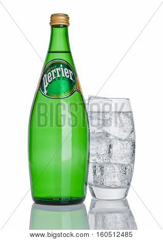 LONDON UK - DECEMBER 06 2016: Bottle and glass with ice of Perrier sparkling water. Perrier is a French brand of natural bottled mineral water sold worldwide.